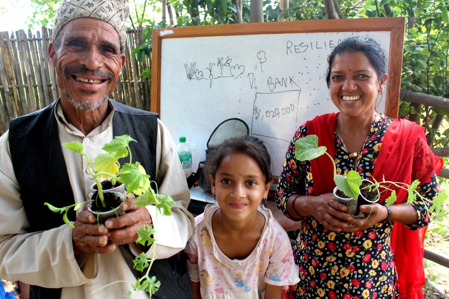 Family in Lubu, Nepal who lost their home smile to receive seeds and starter plants for their garden.