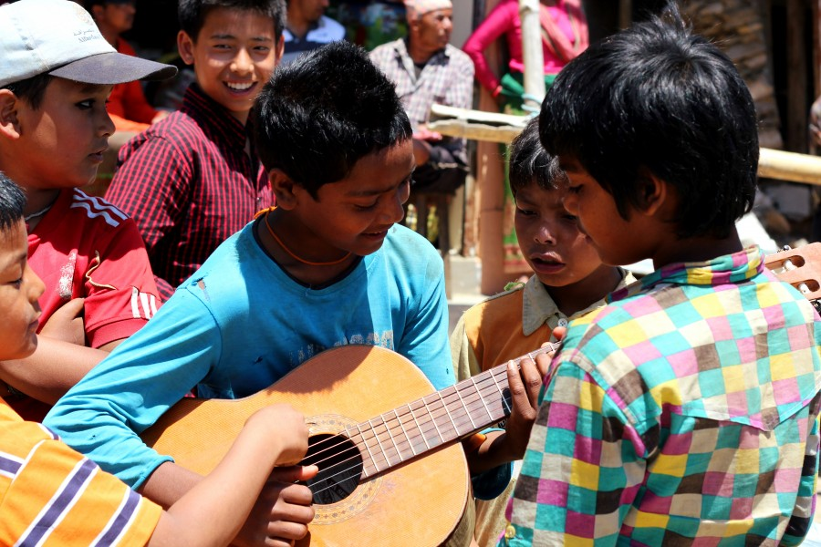 "Kids in Gorkha District playing with the guitar after singing ""Resham Firiri"" joyfully as a group. Photo by Brandon Bodhi Denton"